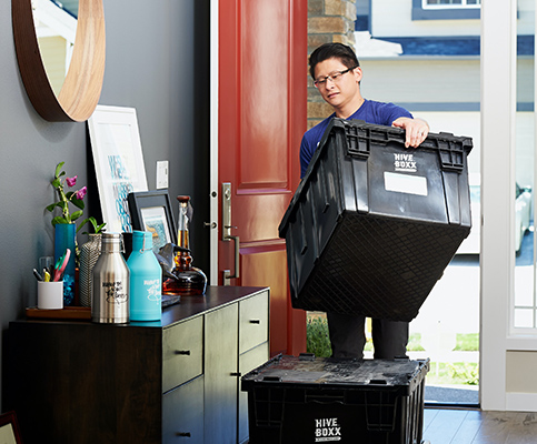 Person carrying plastic bin and moving out of home